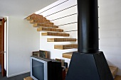 Daring staircase construction with treads projecting from wall and row of horizontal metal rods attached to stove pipe