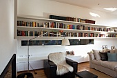 Modern living room with narrow, horizontal window between long bookshelves and sideboard