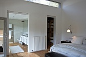 Bedroom with long, slot-shaped transom window, adjacent dressing room and en suite bathroom