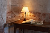 Table lamp and open book on wooden table against wall with faded stencilled pattern
