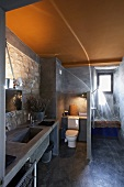 Rustic modern bathroom with stone walls and yellow-painted ceiling