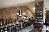 Moderne Küchenzeile vor Natursteinwand im Dachgeschoss