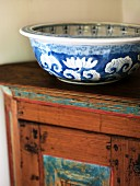 Blue and white ceramic bowl on wooden cabinet