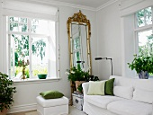 White sofa, house plants and gilt-framed, full-length mirror next to window in living room