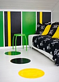 Black throw and cushions on sofa and green stool in attic room with colourful, striped wall