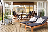 Wooden loungers with cushions on terrace adjoining conservatory