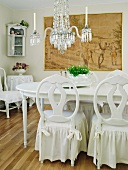 Romantic vintage dining room in white with chandelier and charcoal drawing on wall