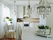 View of kitchen counter in classic-romantic kitchen-dining room with white vintage furniture and chandeliers
