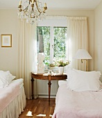 Romantic, vintage-style guest room with classical console table below window and twin beds with valances