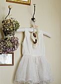 White baby's dress and shoes hanging from wall peg next to posies of dried flowers