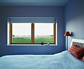 Simple bedroom in light blue and window with a view