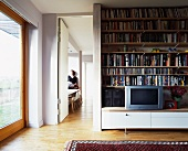 Bücherregal und Fernseher auf bodennahem Sideboard neben offener Tür