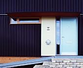 Front door in dark corrugated metal facade with metal ramp