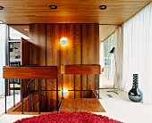 Open head of staircase in front of wood-panelled wall in living space