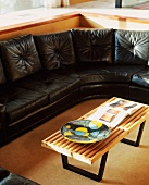 Coffee table with top made of light wooden slats in front of black leather sofa
