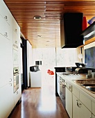 Wooden ceiling above white, fifties-style fitted kitchen