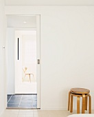 Stacked stools next to open sliding door with view of chair