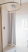 Simple, modern shower with curtain hung on suspended, curved steel tube