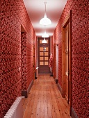 Narrow hall with ornate red and white patterned wallpaper and artificial lighting