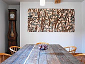 Rustic dining table and chairs in front of abstract picture on wall