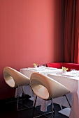 Set tables for two with white and deep pink designer chairs against brick-red wall