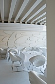 White dining room in Venetian hotel with designer chairs, modern wall relief and expressive ceiling composition