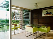 Lime-green armchairs with steel frames at glass table in dining room with view of palm trees