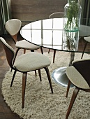 Chairs around glass table with round foot