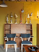 Bureau with desk lamps in front of yellow wall