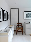 White room with sideboard, old chair and black and white photographs on the walls