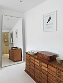 A chest of drawers next to a full-length mirror