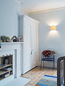 White wardrobe next to converted fireplace containing books and toys