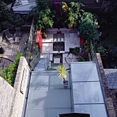 View onto terrace with floor of glass panels and second terrace level with stone flagged floor
