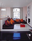 Floor cushion sofas with piles of scatter cushions on pedestal in traditional surroundings
