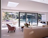 Upholstered furniture collectors' items in modern living space with wide, sliding glass wall and view of sunny terrace