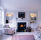 Living room in romantic country house style with floral upholstery and open fireplace between illuminated, fitted shelves