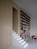 Modern seminar room - stairs formed from single, solid block in front of long, metal bookshelves on wood-clad wall