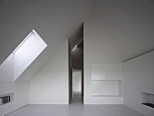 Fitted cupboards in white, modern attic room and view along narrow, high corridor with open door