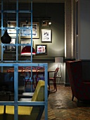 Second-hand chic in London coffee bar with mixture of seating styles between steel frames with glass panels