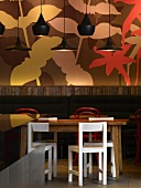 Black pendant lamps in front of trendy floral mural in English coffee bar