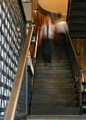 Retro-style staircase in black-brown, folded steel with metal mesh balustrade in London coffee bar