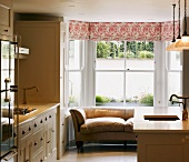 Cream-coloured, retro-style country house kitchen with leather couch in bay window and floral Roman blind