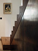 Open living room staircase - sheet metal below wood-clad treads with plate glass balustrade