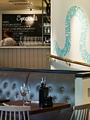 Small, set table in front of leather bench and curved, brass handrail below snaking text mural in London pizza restaurant