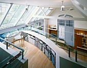 Open-plan, double-height living space - office with teardrop-shaped glass desk and curved storage in gallery balustrade