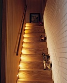 Collection of painted wooden horses on illuminated treads of staircase next to white-painted brick wall