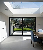 Modern house - wide sliding terrace door with view of garden and sloping skylight above sunny dining area