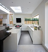 Sunny, designer kitchen with sophisticated two-tone colour scheme featuring modern mineral materials and dark wood counter
