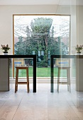 Reflection of counter with bar stool in front of panoramic window with view of garden