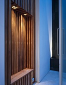Illuminated wood-clad niche with narrow bench